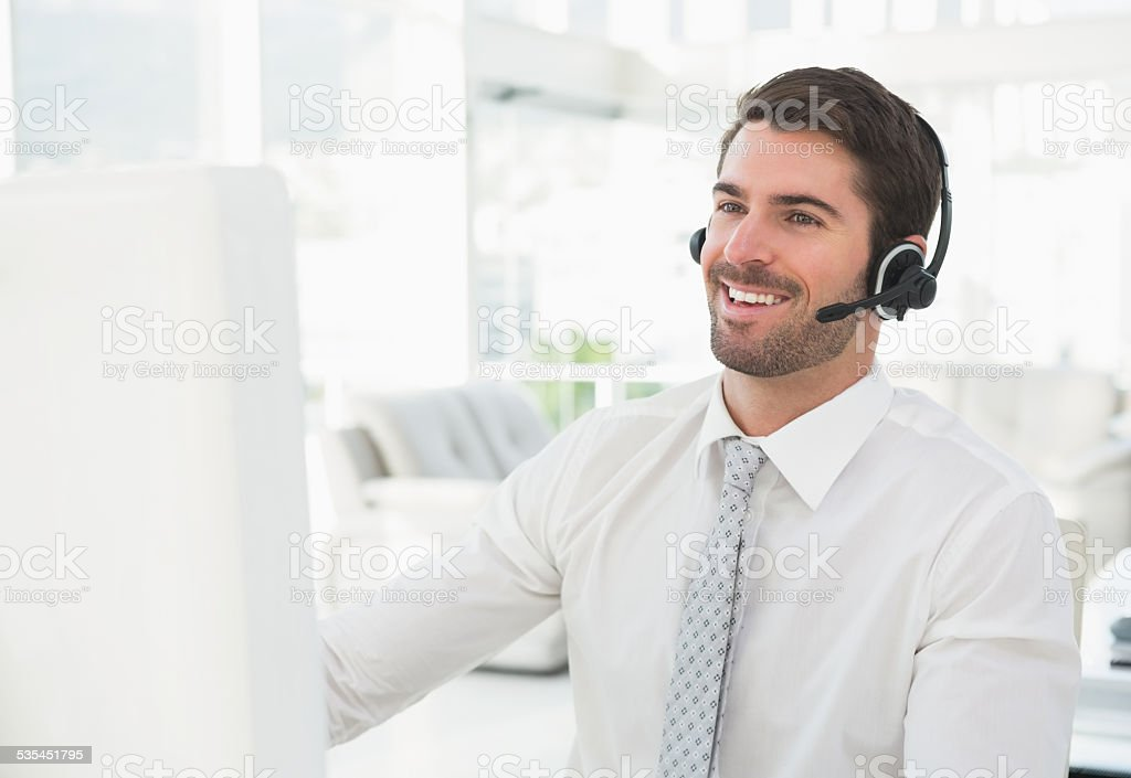 Smiling businessman with headset interacting stock photo