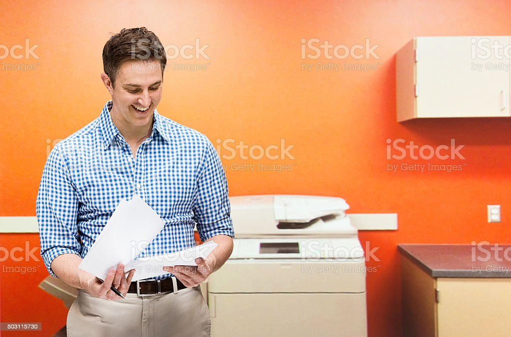 Smiling businessman working in office stock photo