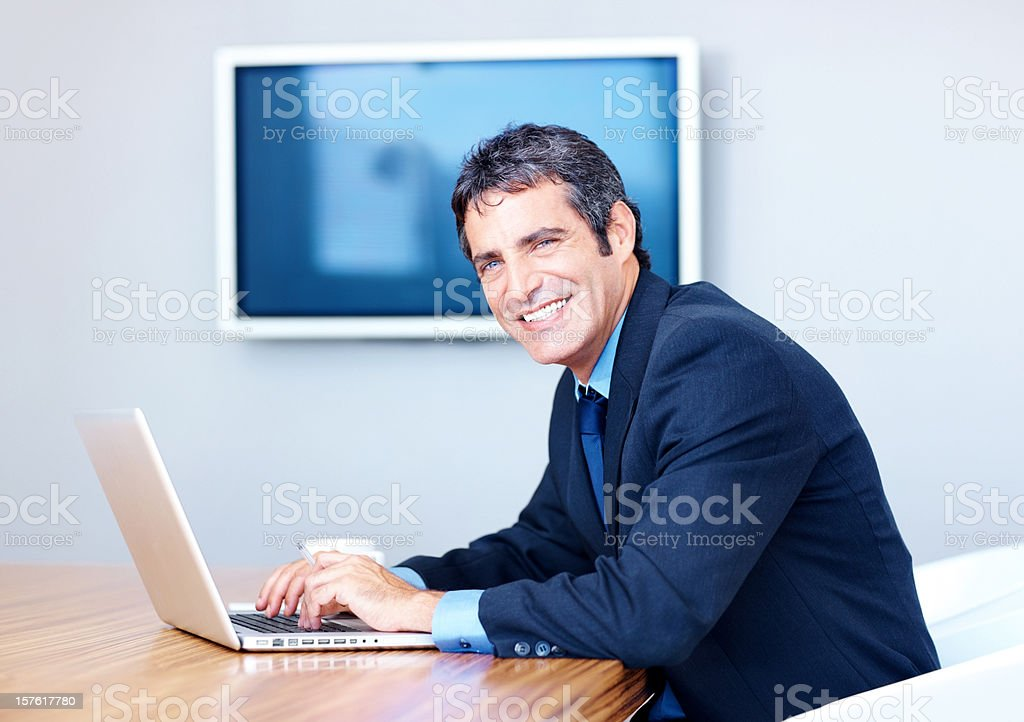 Smiling businessman working on a laptop royalty-free stock photo