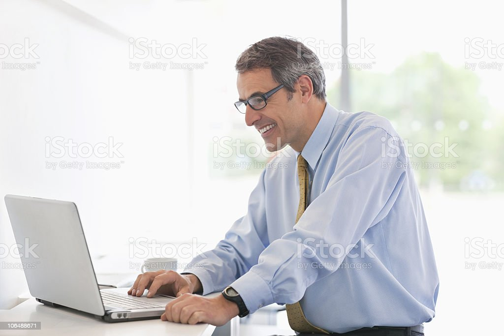 Smiling businessman working on laptop in office cafeteria royalty-free stock photo