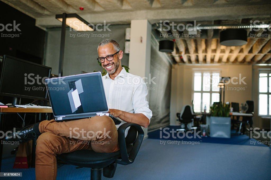 Smiling businessman working on laptop stock photo