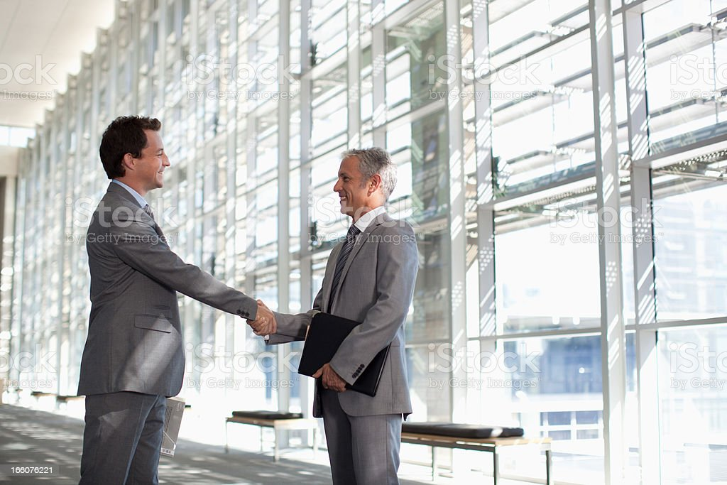 Smiling businessmen shaking hands in modern lobby royalty-free stock photo