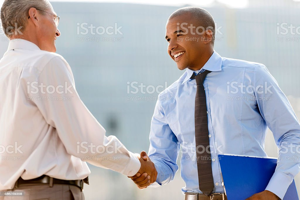 Smiling businessmen shaking hands outdoors. stock photo