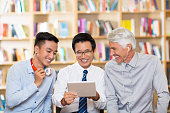 Smiling businessmen using tablet in library