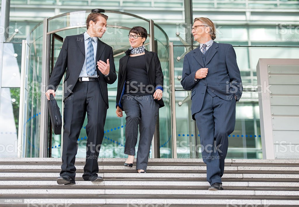 Smiling businesspeople walking down the stairs and communicating stock photo