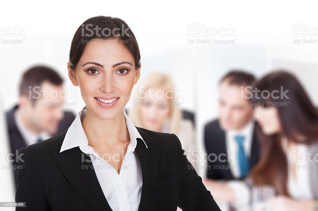 Sonriente mujer de negocios con equipo de hablar en la sala de juntas - foto de stock