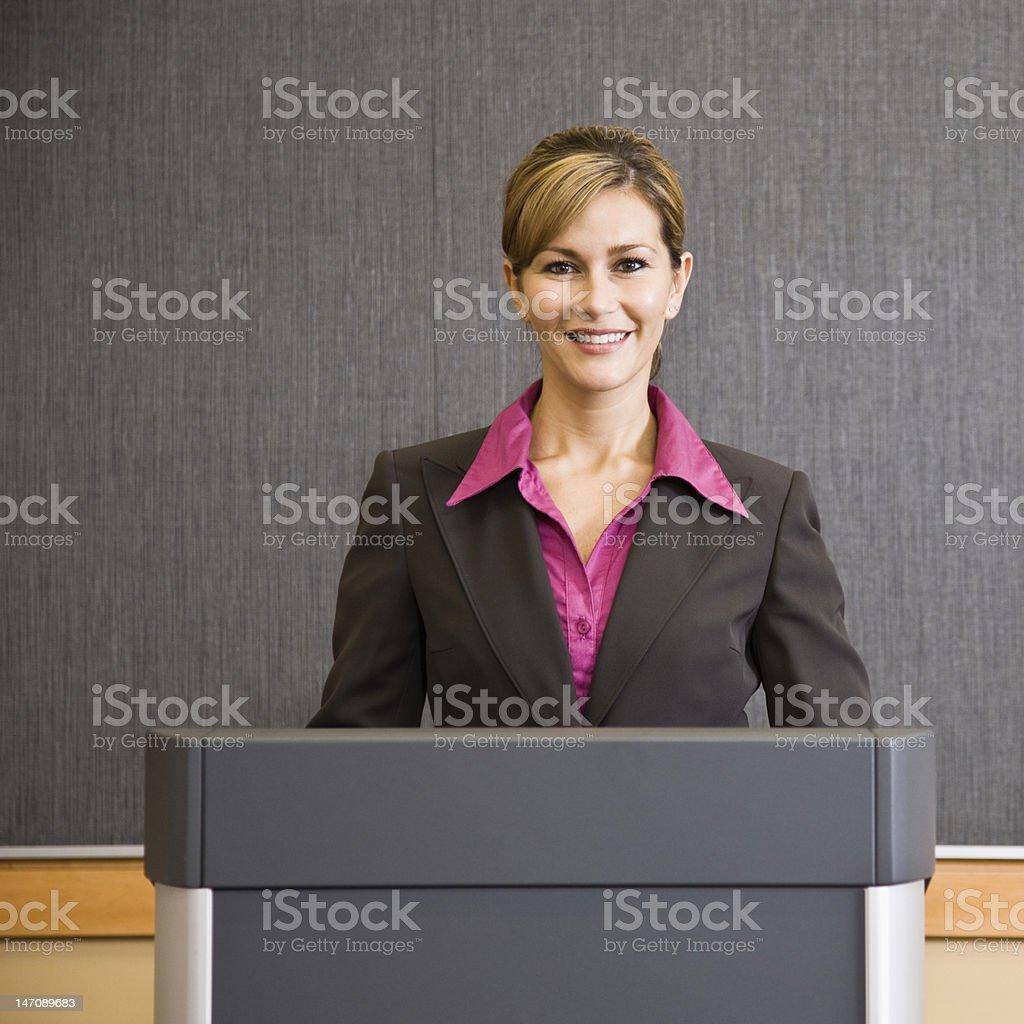 Smiling Businesswoman At Podium stock photo
