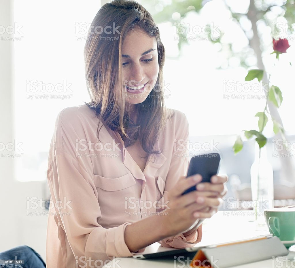 Smiling businesswoman checking cell phone stock photo