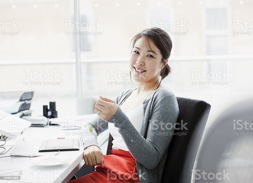 Smiling businesswoman drinking coffee at desk in office stock photo