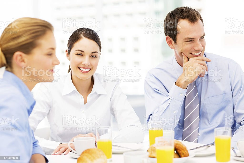 Smiling Businesswoman Having Breakfast With Colleagues royalty-free stock photo