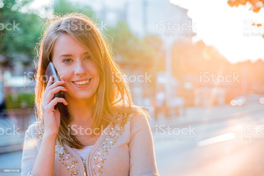 Smiling businesswoman  having pleasant conversation on mobile ph stock photo
