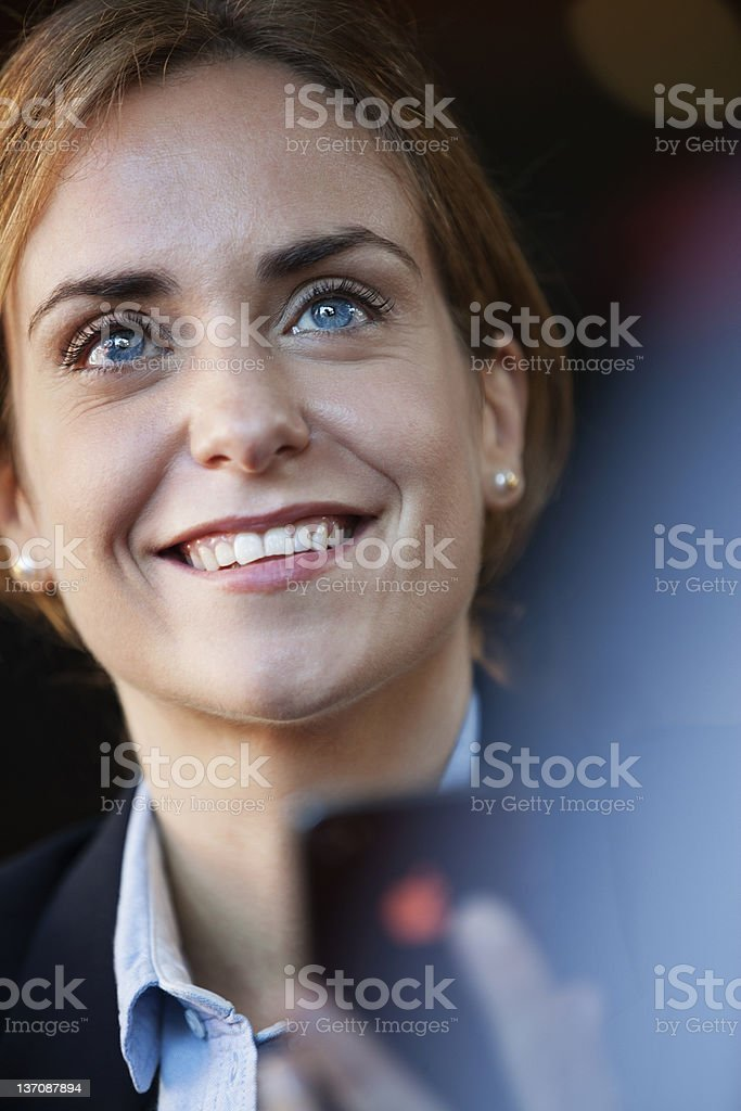 Smiling businesswoman holding cell phone royalty-free stock photo