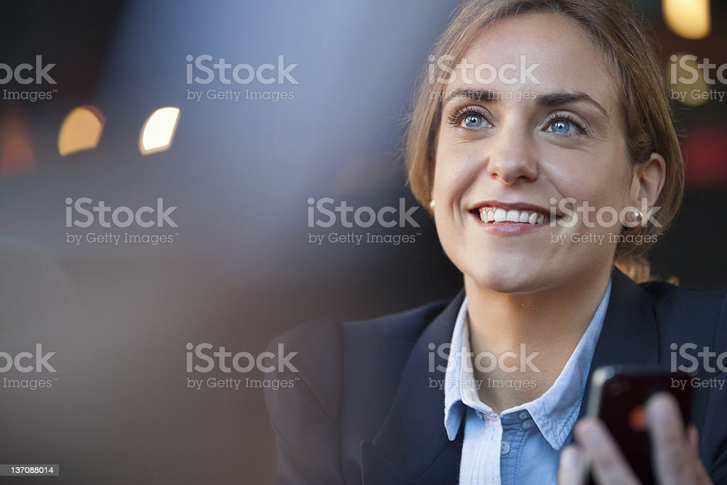 Smiling businesswoman holding cell phone stock photo