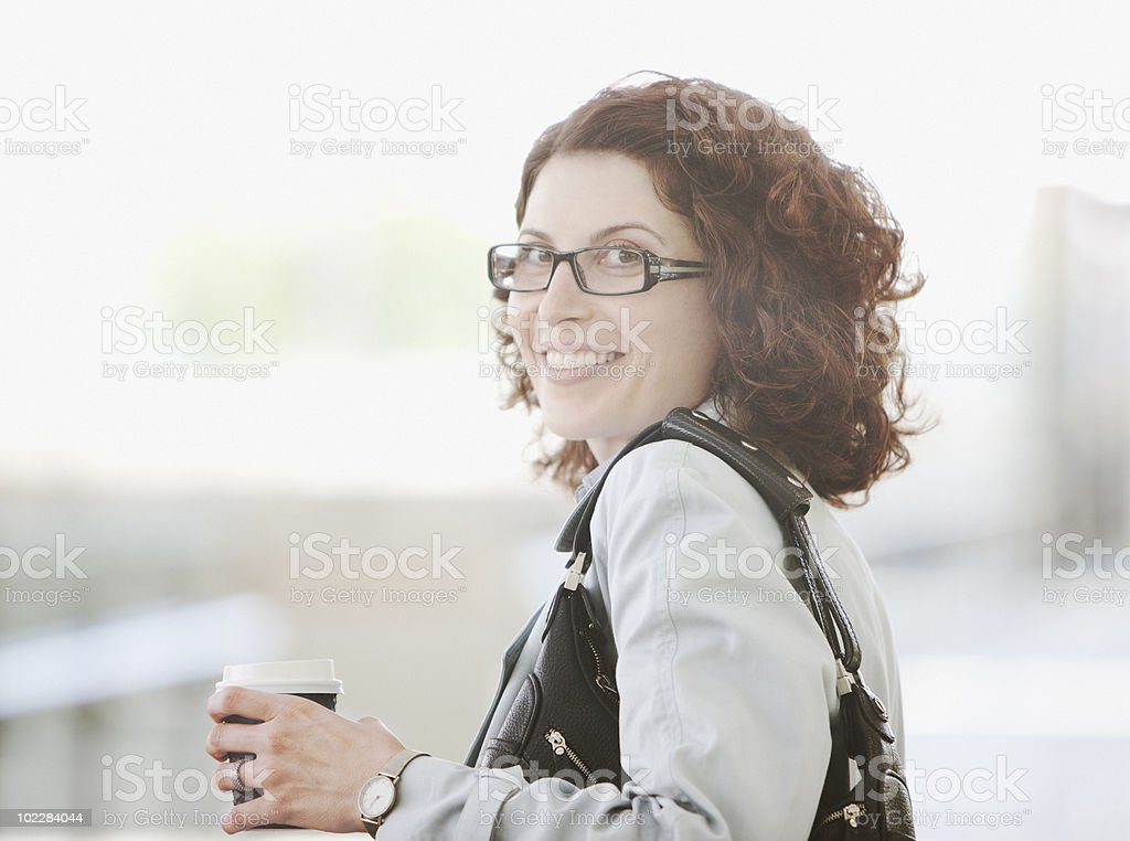 Smiling businesswoman holding coffee royalty-free stock photo