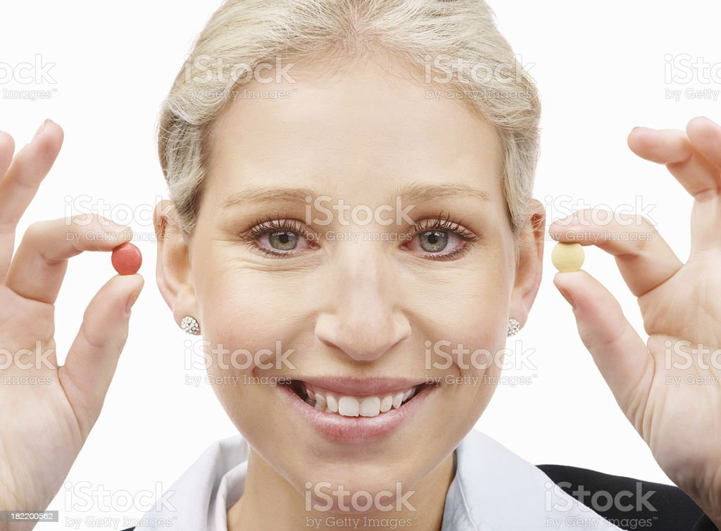 Smiling businesswoman holding different pills stock photo