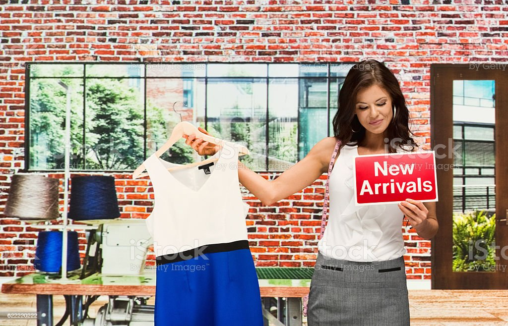 Smiling businesswoman holding new arrivals sign stock photo