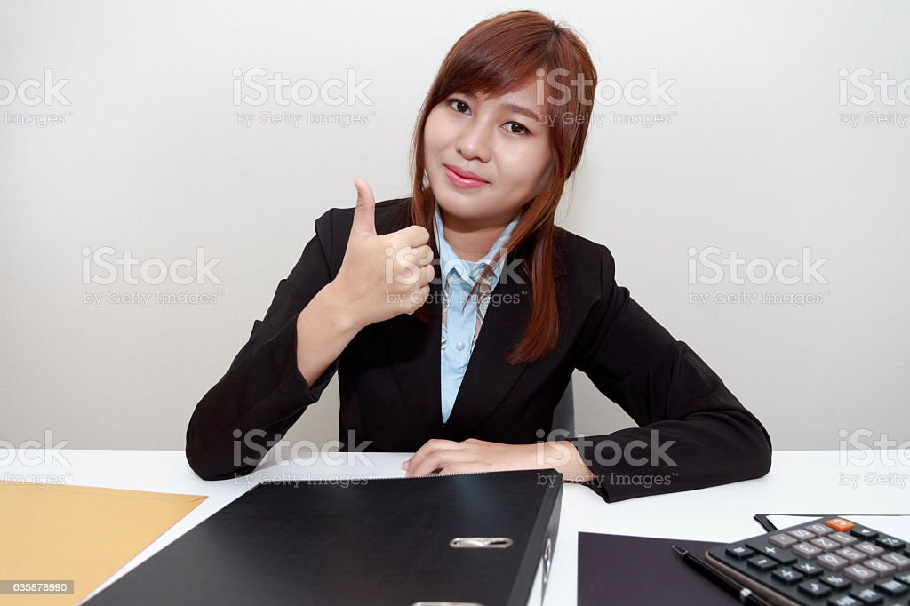 Smiling businesswoman holding thumps up at office with calculator stock photo