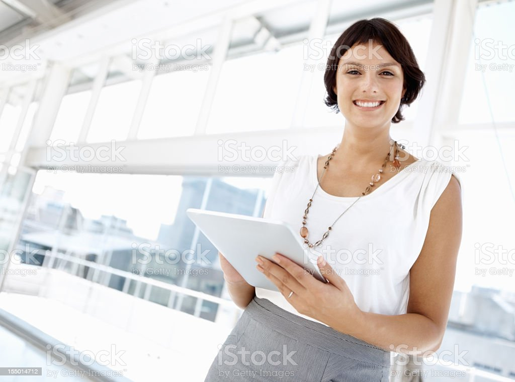 Smiling businesswoman in a sunny atrium with a white tablet royalty-free stock photo