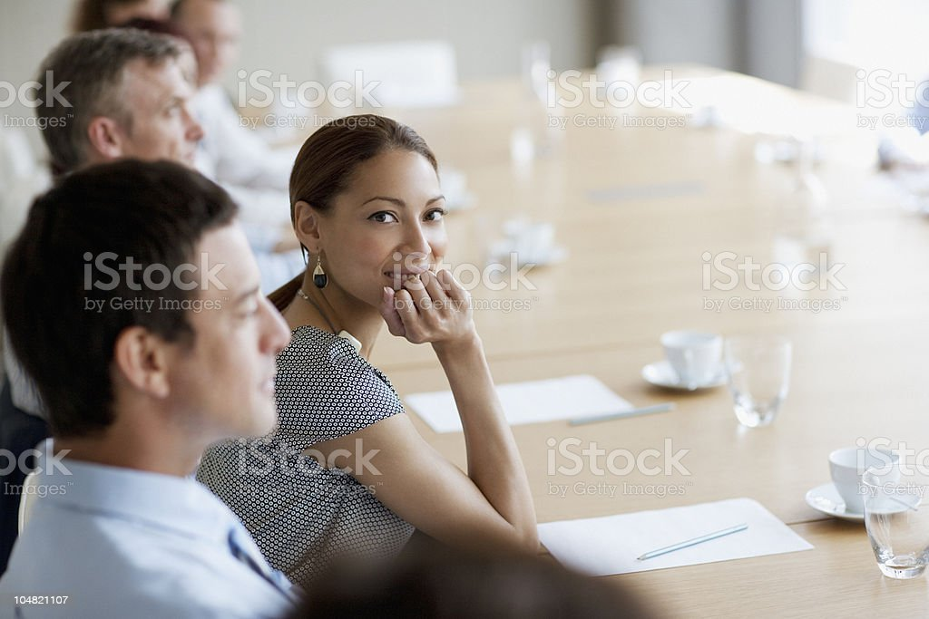Smiling businesswoman in meeting in conference room stock photo