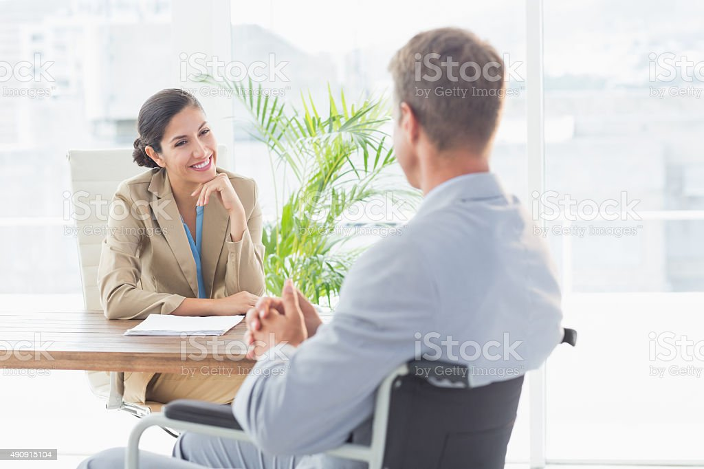 Smiling businesswoman interviewing disabled candidate stock photo