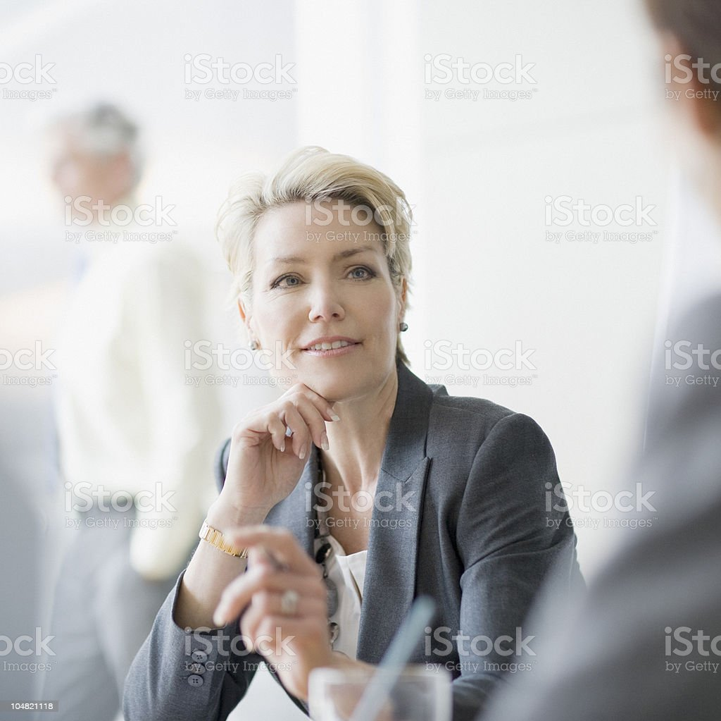 Smiling businesswoman listening stock photo