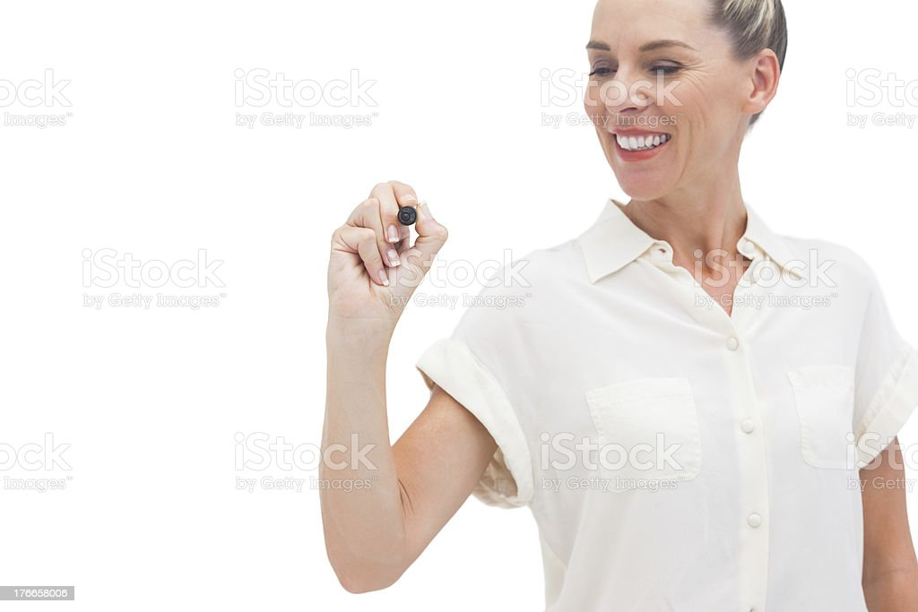 Smiling businesswoman looking at pen in her hand royalty-free stock photo