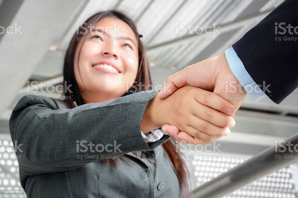 Smiling businesswoman making handshake with a businessman stock photo