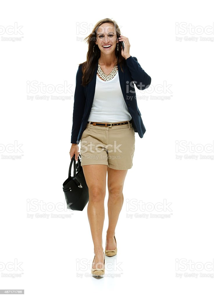 Smiling businesswoman on mobile and walking stock photo