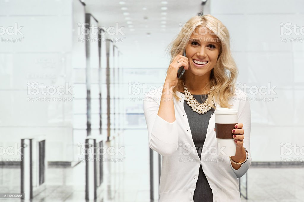 Smiling businesswoman on phone in office stock photo