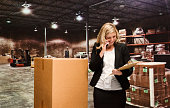 Smiling businesswoman on phone in warehouse
