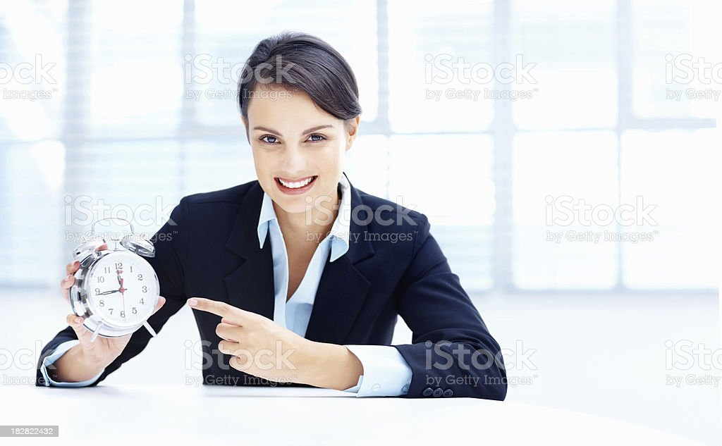 Smiling businesswoman pointing at an alarm clock royalty-free stock photo