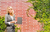 Smiling businesswoman pointing at tablet