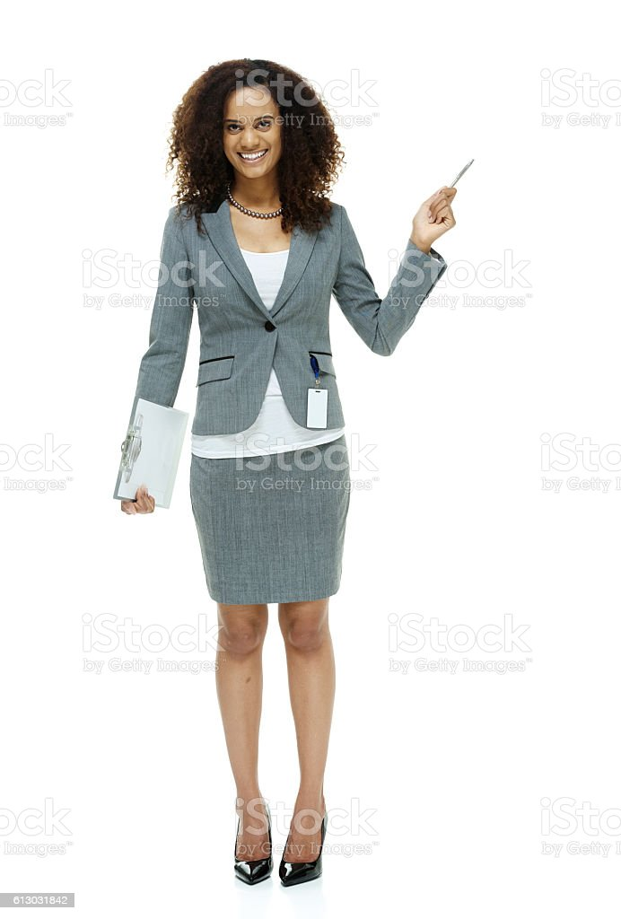 Smiling businesswoman pointing away stock photo