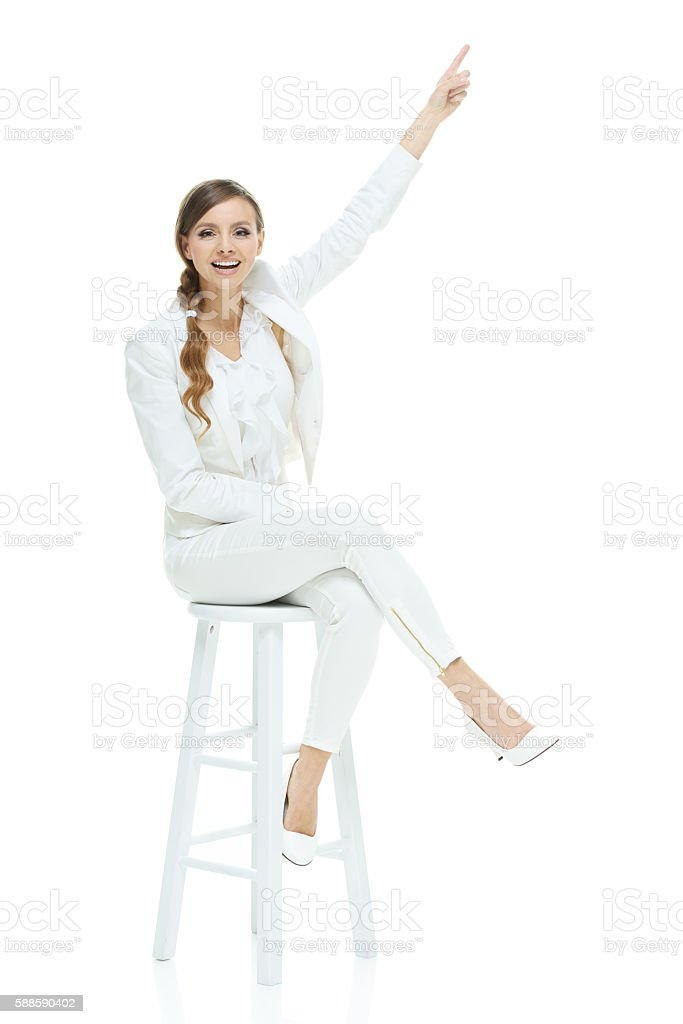 Smiling businesswoman pointing up stock photo