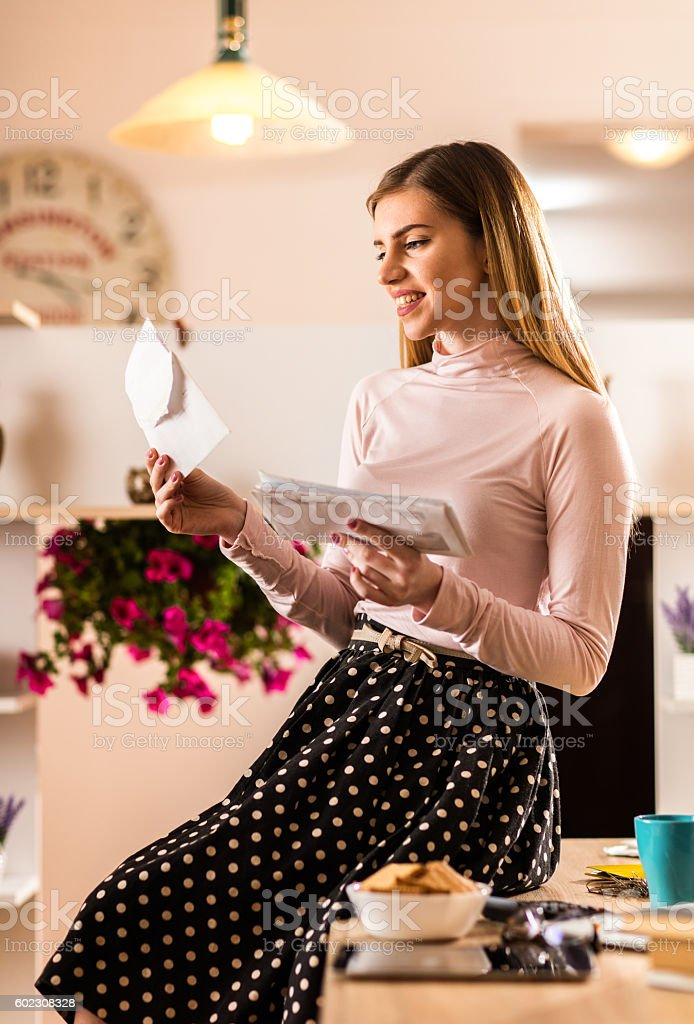 Smiling businesswoman reading mail letters in the office. stock photo