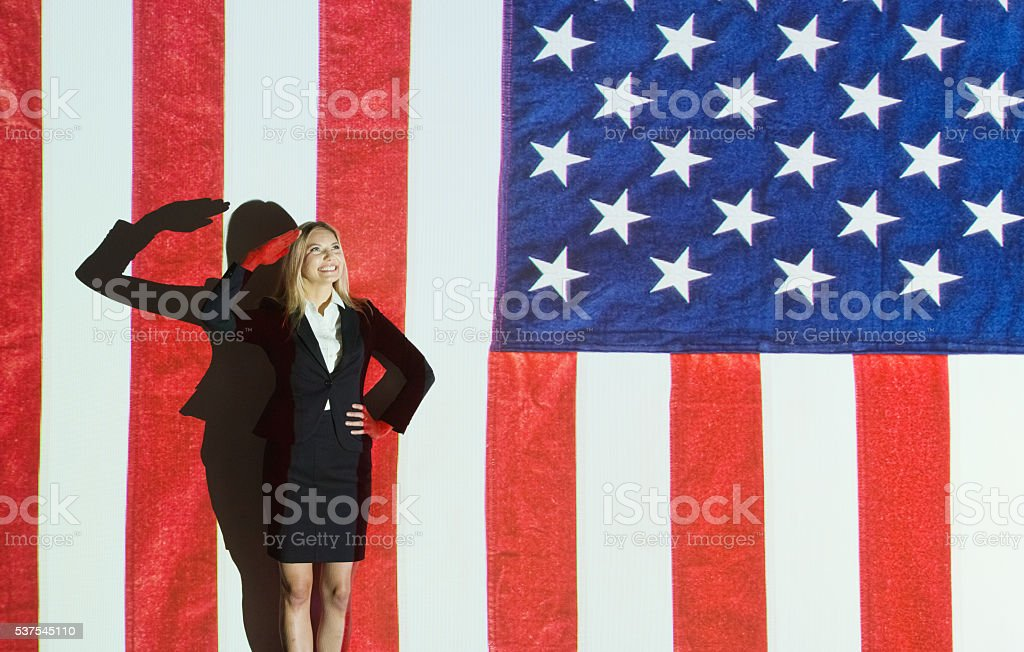 Smiling businesswoman saluting stock photo