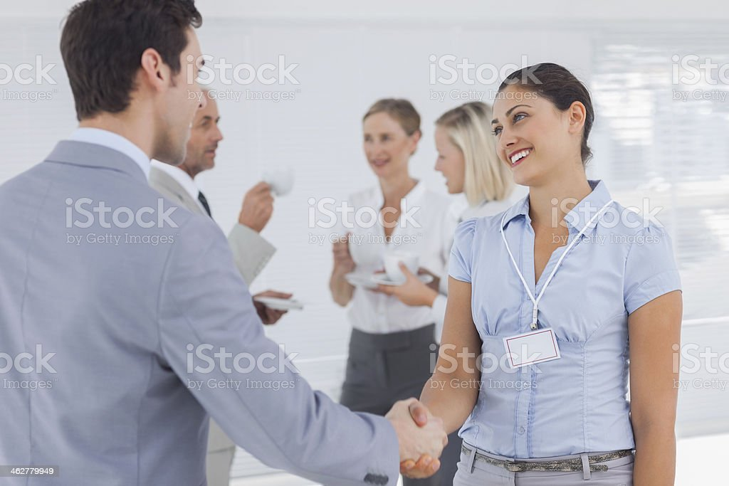 Smiling businesswoman shaking hand of a colleague stock photo