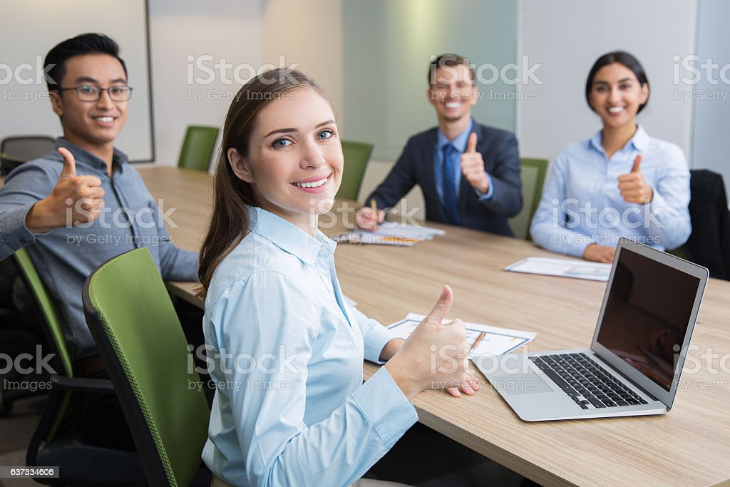 Smiling businesswoman showing thumb at conference stock photo