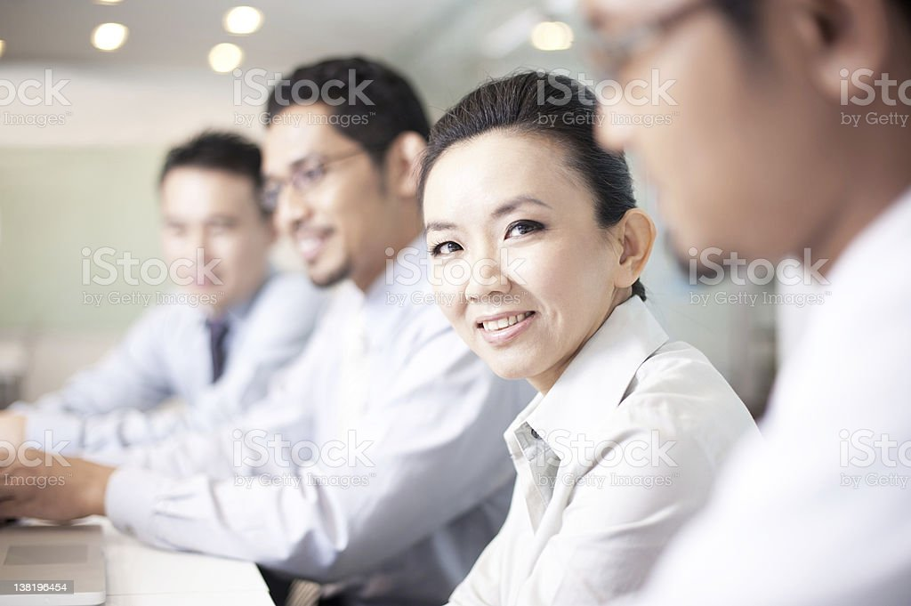 Smiling businesswoman sits with male colleagues royalty-free stock photo