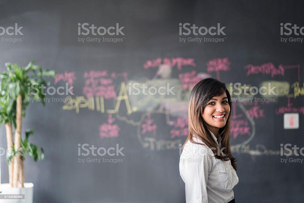 Smiling businesswoman standing against blackboard stock photo