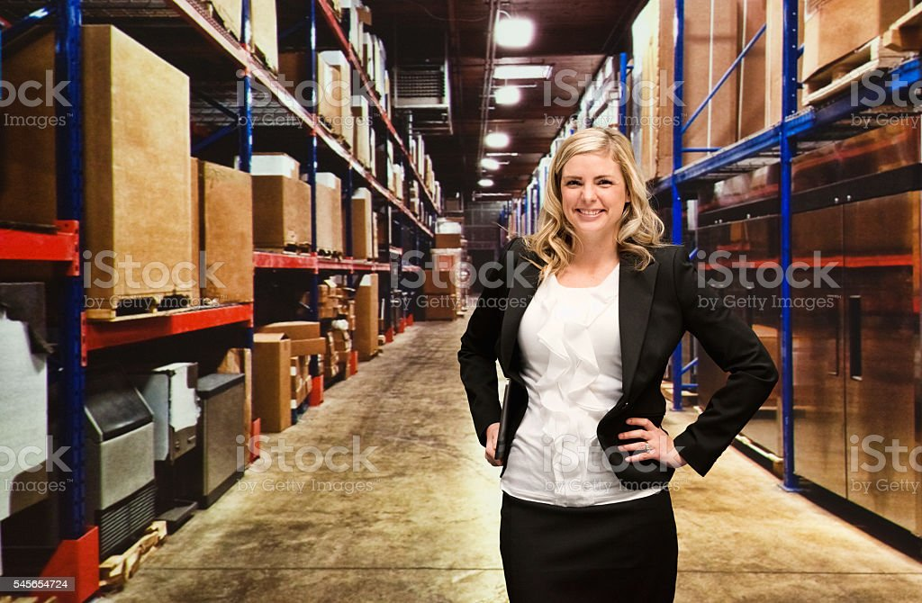Smiling businesswoman standing in warehouse stock photo