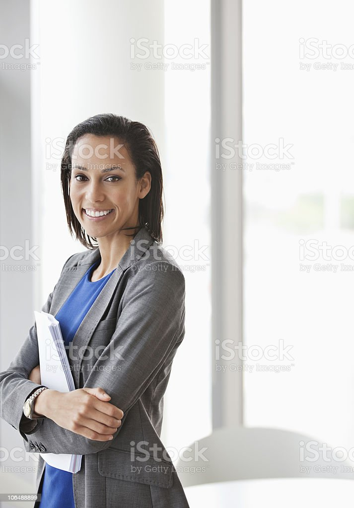Smiling businesswoman standing with documents in office, portrait royalty-free stock photo
