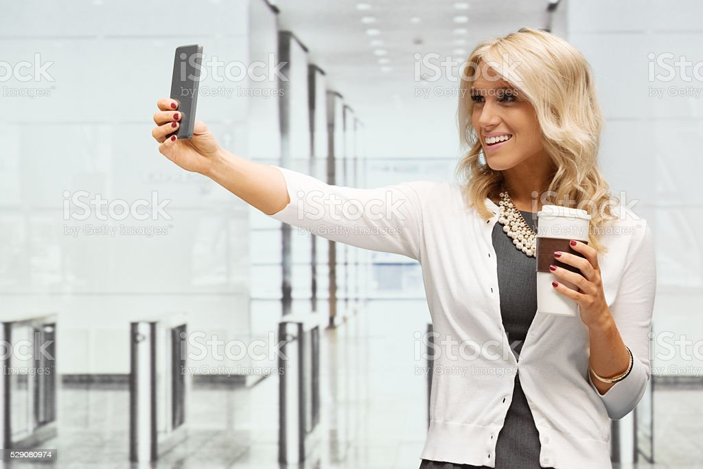 Smiling businesswoman taking a selfie stock photo