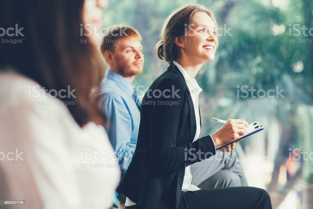 Smiling Businesswoman Taking Notes at Conference stock photo