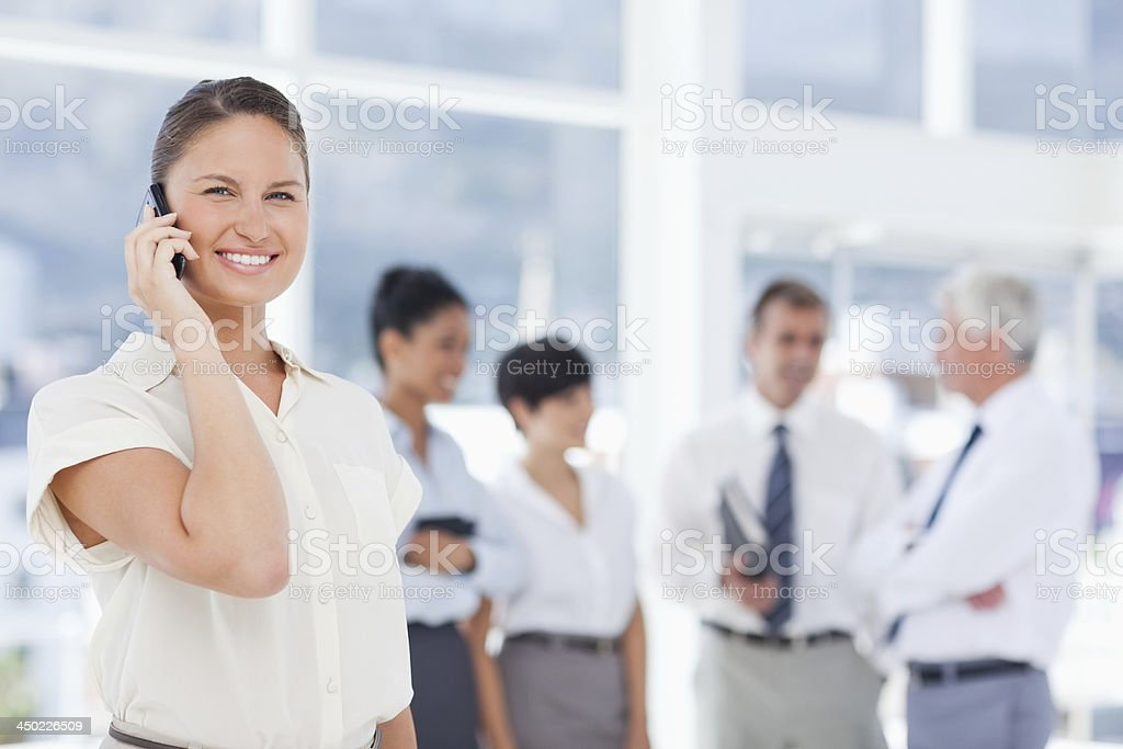 Smiling businesswoman talking on her cellphone with colleagues stock photo