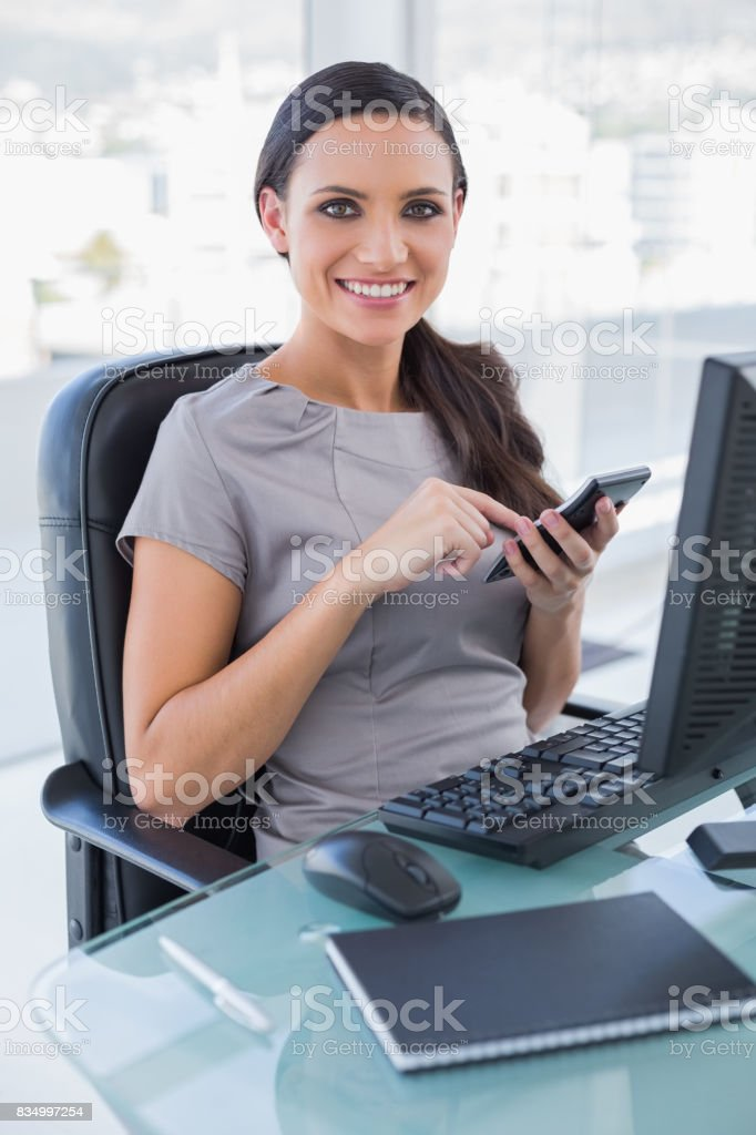 Smiling businesswoman using calculator stock photo