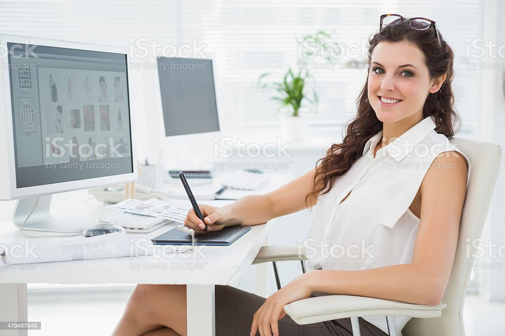 Smiling businesswoman using digitizer at desk stock photo