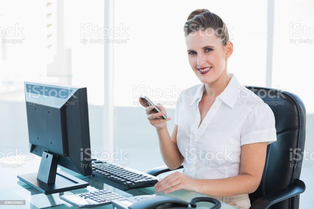 Smiling businesswoman using mobile phone stock photo
