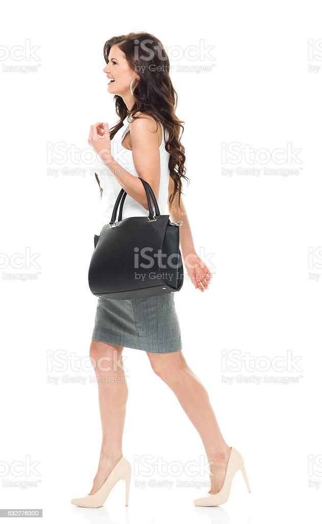 Smiling businesswoman walking stock photo