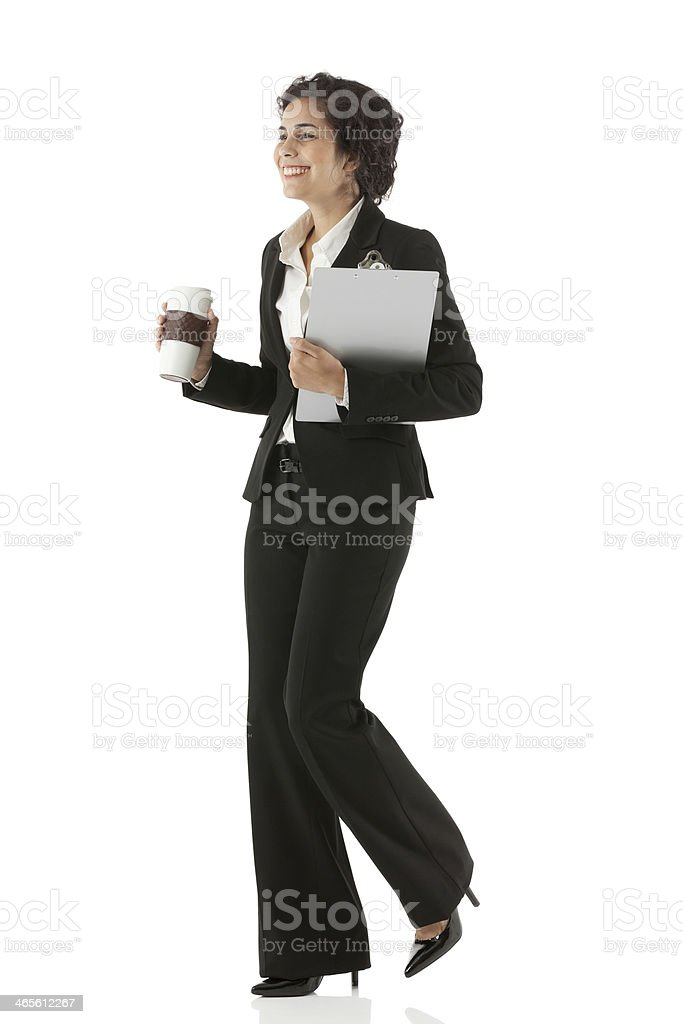 Smiling businesswoman walking with coffee royalty-free stock photo